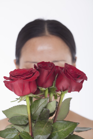 obscured: Shirtless woman behind a bunch of beautiful red roses, obscured face, studio shot