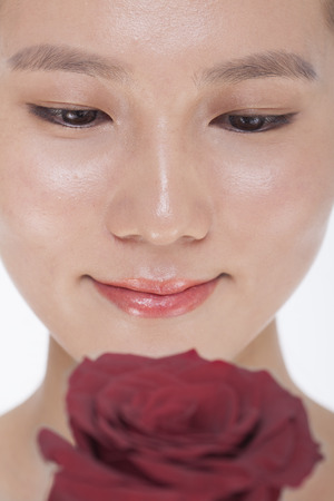 woman looking down: Close-up on the face of smiling beautiful woman looking down at a red rose, studio shot Stock Photo