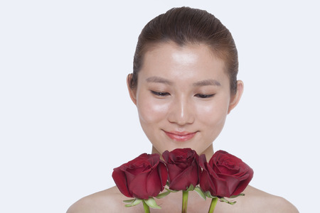 woman looking down: Young, beautiful, smiling woman looking down at a bunch of red roses, studio shot