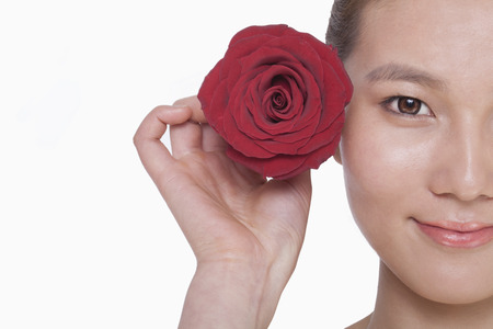 Smiling young woman holding up a red rose next to her ear, studio shot photo