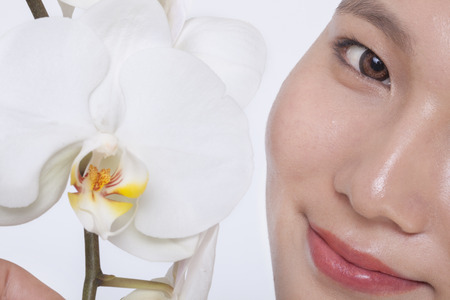 above 21: Close up of young woman smiling and a beautiful white flower, half face showing, studio shot