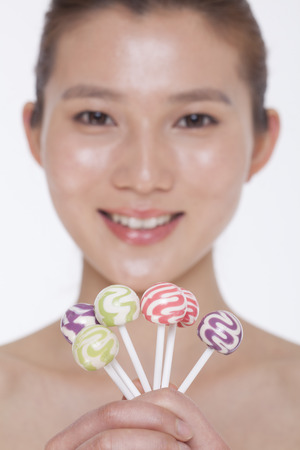 above 21: Smiling young woman looking into camera and holding up colorful lollipops, studio shot Stock Photo