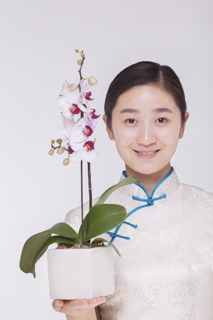 above 21: Portrait of smiling young woman holding a beautiful white flower in a flower pot, studio shot Stock Photo