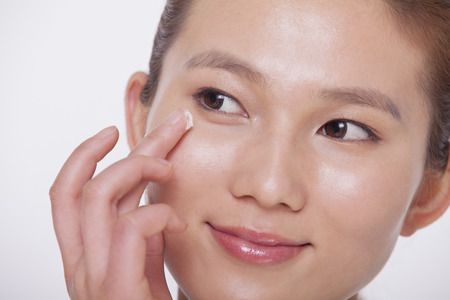 above 21: Close up on the face of a smiling young woman applying cream to her face, studio shot
