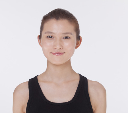 tank top: Portrait of smiling beautiful young woman in a black tank top, studio shot