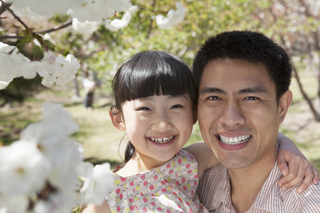 some under 18: Smiling father and daughter enjoying the cherry blossoms on the tree in the park in springtime, portrait