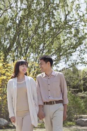 above 30: Happy couple holding hands and going for a walk in the park in springtime, Beijing Stock Photo