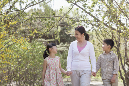 Grandmother holding hands with her two grandchildren and going for a walk in the park in springtime