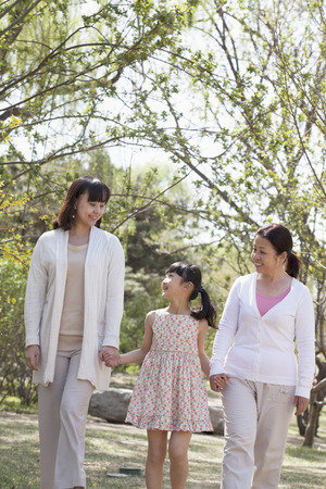 some under 18: Multi-generational family, grandmother, mother, and daughter holding hands and going for a walk in the park in springtime
