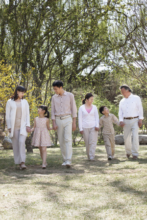 some under 18: Happy smiling family holding hands and going for a walk in the springtime, standing in a row