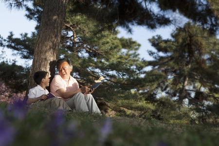 some under 18: Grandfather and grandson relaxing under a tree and reading books in a park in the springtime, Beijing