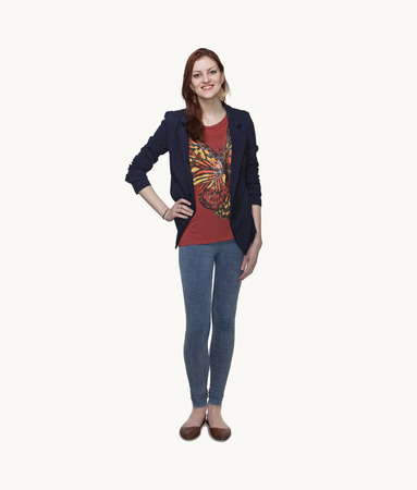 above 18: Portrait of smiling young woman in casual clothing, hand on hip, full length, studio shot