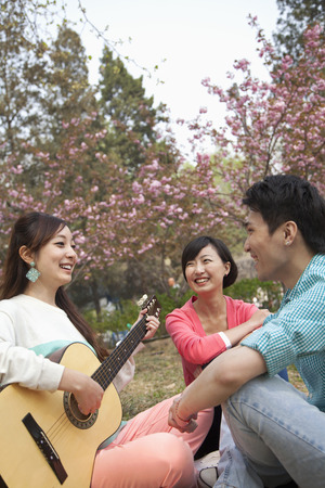 above 21: Young happy friends hanging out in the park in springtime, playing guitar