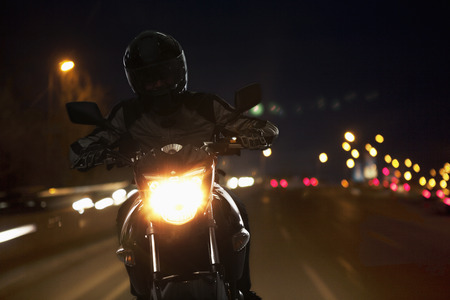 Young Man riding a motorcycle at night through the streets of Beijing Standard-Bild