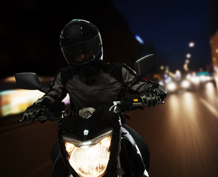 above 25: Young Man riding a motorcycle at night through the streets of Beijing Stock Photo