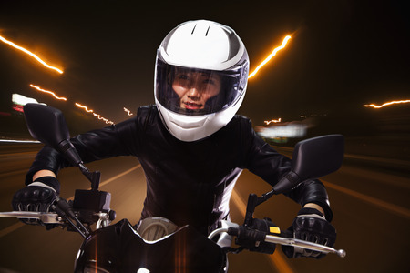 above 25: Young woman riding a motorcycle through the streets of Beijing, light trails