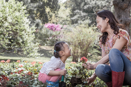 some under 18: Mother and daughter planting flowers.