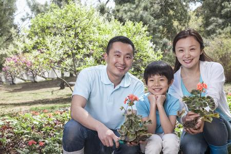 Portrait of family planting flowers. photo