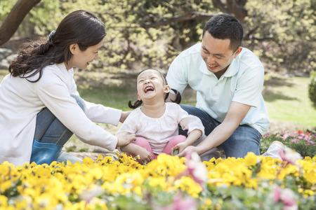 some under 18: Family sitting in flower garden.