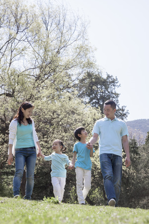 some under 18: Family holding hands, walking in park. Stock Photo