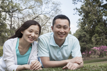 above 30: Portrait of couple lying in grass in park.