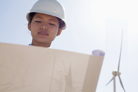 above 21: Young female engineer holding open and looking down at blueprints, on site with wind turbines