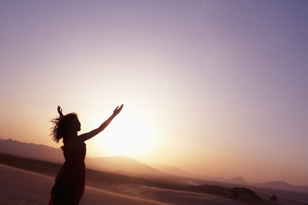 above 21: Serene young woman with arms outstretched doing yoga in the desert in China, Silhouette Stock Photo