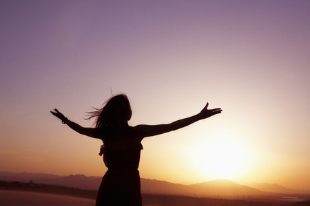 outstretched: Serene young woman with arms outstretched doing yoga in the desert in China, Silhouette Stock Photo
