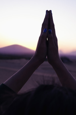 above 21: Serene young woman with her palms together in prayer held above her head in the desert in China, close-up Stock Photo