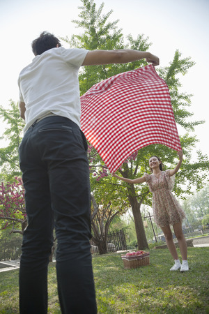 above 18: Two friends opening up a checkered blanket and getting ready to have a picnic in the park