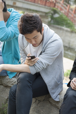 above 18: Young man in a gray hooded sweatshirt looking down at his phone and texting outdoors Stock Photo