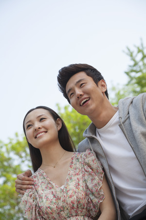 arm around: Smiling happy young couple with arm around the shoulders outdoors in a park, front view Stock Photo