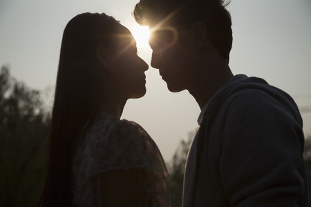 above 18: Silhouette of young couple very close to each other, sunbeam and lens flare