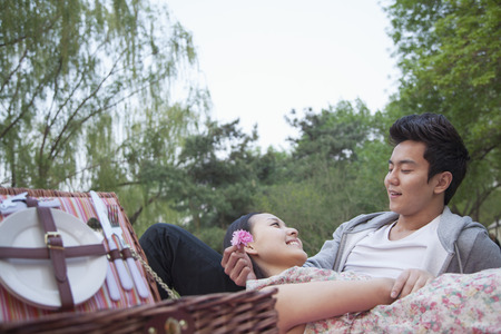 ピクニック バスケット オープンと毛布の上に横になって、公園でピクニックを持つ愛のカップルの笑顔 写真素材