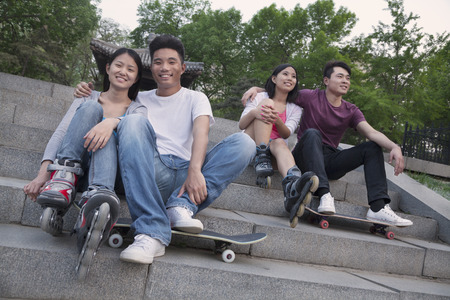 above 18: Two young couples sitting and resting on concrete steps outside with skateboards and roller blades
