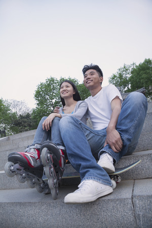 above 18: Young happy couple sitting and resting on concrete steps outside with a skateboard and roller blades Stock Photo