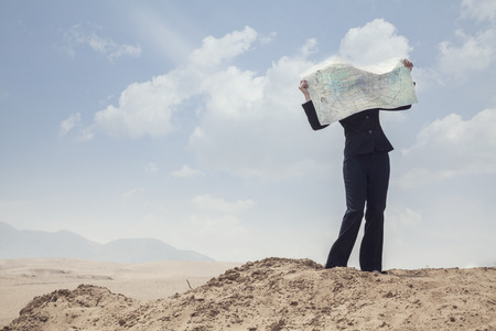 Young Businesswoman looking at a map in the middle of the desert  photo