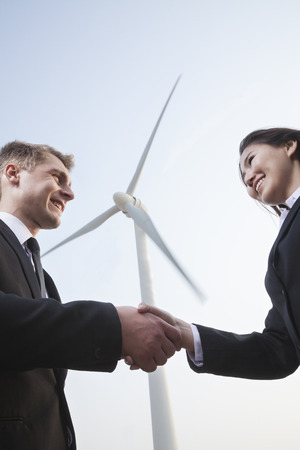 above 21: Two smiling young business people shaking hands in front of a wind turbine Stock Photo