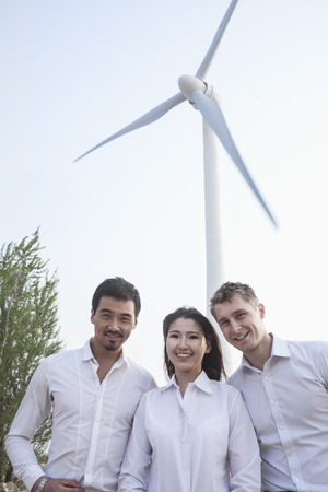 three day beard: Portrait of three young business people standing in front of a wind turbine, looking at camera Stock Photo
