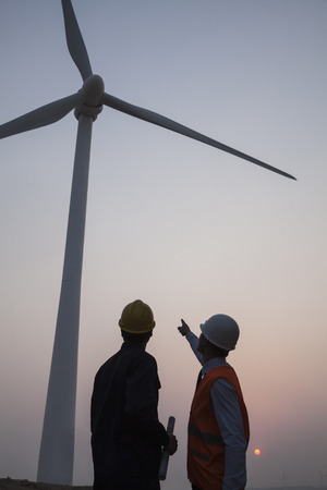 energy work: Two young male engineers standing beside a wind turbine at sunset, pointing up