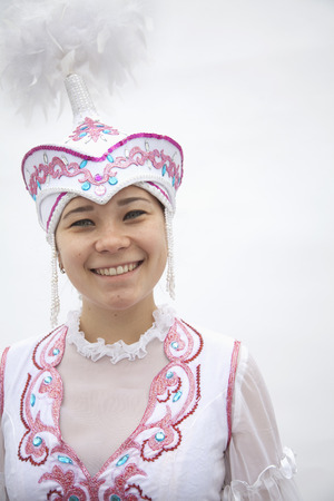 above 21: Portrait of young smiling woman in traditional clothing from Kazakhstan, studio shot Stock Photo