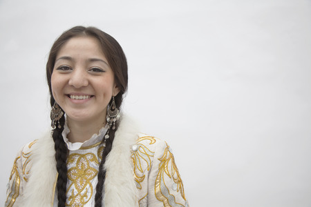 above 21: Portrait of young smiling woman with braids in traditional clothing from Kazakhstan, studio shot