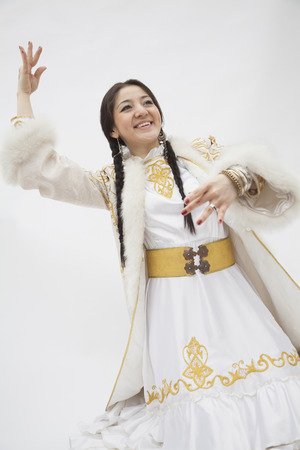 above 21: Portrait of young dancing woman with braids in traditional clothing from Kazakhstan, studio shot Stock Photo