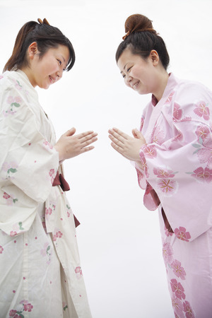 above 21: Two young smiling  woman in Japanese kimonos bowing to each other, studio shot