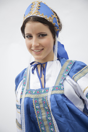 above 21: Portrait of young smiling woman in traditional clothing from Russia, studio shot