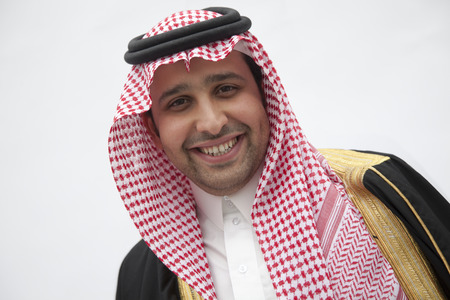 above 21: Portrait of smiling young man in traditional Arab clothing and Kaffiyeh, studio shot Stock Photo