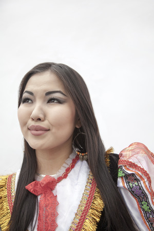 above 21: Portrait of young smiling woman in traditional clothing, studio shot