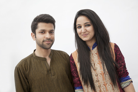 indian culture: Portrait of smiling young couple wearing traditional clothing from Pakistan, studio shot Stock Photo