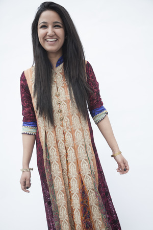 above 21: Portrait of smiling young woman wearing traditional clothing from Pakistan, studio shot Stock Photo