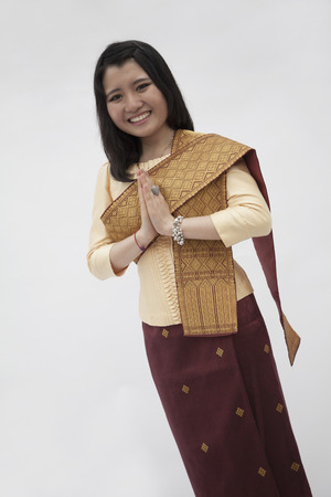hands clasped: Portrait of smiling young woman with hands clasped together in traditional clothing from Laos, studio shot